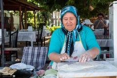 梅尔辛,土耳其- 2018年6月14日:准备传统土耳其未膨松面制面包的eldery土耳其妇女 免版税库存图片