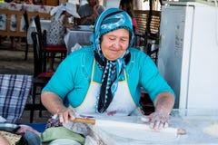 梅尔辛,土耳其- 2018年6月14日:准备传统土耳其未膨松面制面包的eldery土耳其妇女 图库摄影