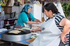 梅尔辛,土耳其- 2018年6月14日:准备传统土耳其未膨松面制面包的eldery土耳其妇女 库存照片