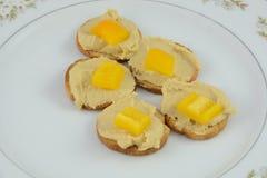 梅尔巴吐司、hummus和切好的黄色喇叭花peppe开胃菜  图库摄影
