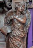 梅赫伦-与Inri题字的被雕刻的天使雕象从Onze辛迪里夫Vrouw VA n-Hanswijkbasiliek教会 免版税图库摄影
