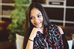 年轻梦中情人画象咖啡馆的 美丽的女孩在咖啡店坐,并且神色,微笑的女孩,在面孔附近递 库存图片