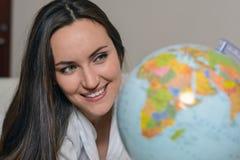 梦想冒险 睡衣的特写镜头微笑的妇女观看地球的 旅途计划的概念 免版税库存照片