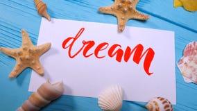 梦想文本 在白色帆布的诱导词上写字字体与由书法家的红色墨水 贝壳和海星 股票录像