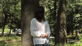 梦想的女孩倾斜反对树的树干,微笑并且放松 影视素材