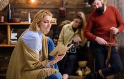 梦想的女性读书引人入胜的书,幻想世界概念 蓝色衬衣、的牛仔裤和坐米黄的雨披的妇女  库存照片