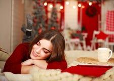 梦想的妇女在圣诞节背景的床上说谎  免版税库存照片