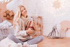 年轻梦想的妇女有圣诞节礼物在她的手 库存图片