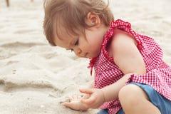 梦想的子项 逗人喜爱的深色头发的坐腰臀部分和使用与沙子的孩子微小的小孩女婴在海滩  库存图片