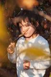 梦想的小女孩在附近保留草茎  免版税图库摄影