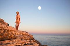 梦想的男孩敬佩在天空的被迷惑的月亮 图库摄影