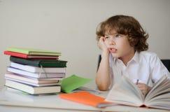 梦想的男小学生做他的家庭作业 库存图片