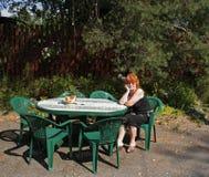 梦想的红发妇女在桌上在她的庭院里 免版税库存图片