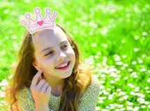 梦想的面孔的女孩花费休闲户外 摆在与照相讲席会的纸板冠的孩子在草甸 公主 免版税图库摄影