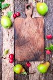梨和小苹果在空的切板附近在木土气背景 顶视图 框架 秋天收获拷贝空间 图库摄影