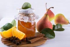 梨和橙色果酱在玻璃瓶子用成熟梨、肉桂条、茴香星和绿色在桌离开 免版税库存图片