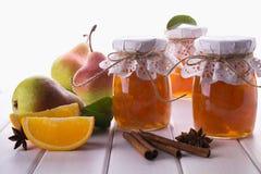 梨和橙色果酱在玻璃瓶子用成熟梨、肉桂条、茴香星和绿色在桌离开 库存图片