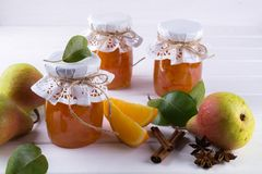 梨和橙色果酱在玻璃瓶子用成熟梨、肉桂条、茴香星和绿色在桌离开 免版税库存照片