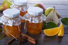梨和橙色果酱在玻璃瓶子用成熟梨、肉桂条、茴香星和绿色在桌离开 库存照片