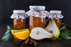 梨和橙色果酱在玻璃瓶子用成熟梨、肉桂条、茴香星和绿色在桌离开 免版税图库摄影
