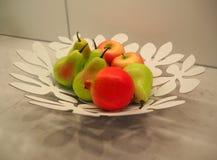 梨和苹果在板材作为厨房用桌的装饰 图库摄影