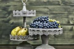 梨和葡萄在黑暗的木头 免版税库存照片