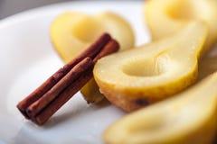 梨在糖浆烹调了用肉桂条 免版税库存照片