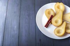 梨在糖浆烹调了用肉桂条 图库摄影