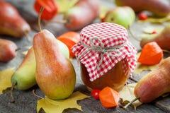 梨果酱和成熟梨在老木桌上 仍然秋天生活 图库摄影