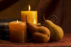 梨蜡烛和书 免版税图库摄影