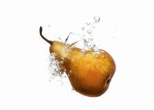 梨滴下了入在白色的水飞溅 免版税图库摄影