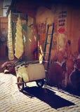 梯子和推车对墙壁在马拉喀什日落的 免版税库存图片