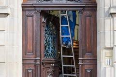 梯子的人清洗的房子 库存图片