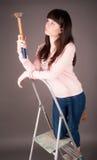 梯子的可爱的妇女与锤子 免版税库存图片