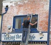 梯子的工作员更新商店前面的 免版税库存照片