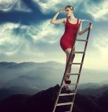 梯子的端庄的妇女 库存图片