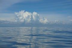 梯度蓝天天际自然本底场面和在深蓝色海水上的蓬松白色云彩起波纹结冰的行动 库存图片