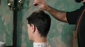梳一个男性客户的头发的围裙的有胡子的理发师坐在椅子在理发店 慢照相机圆的运动 股票录像