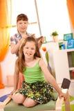 梳乐趣有女孩的头发年轻人 免版税库存照片