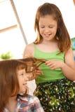 梳享用女孩头发年轻人 图库摄影