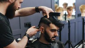 梳和刮一个男性客户的头发的男性理发师 库存照片