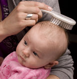 梳头发母亲的婴孩 免版税库存图片
