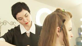 梳女性理发前面镜子的美发师长的头发在理发沙龙 关闭做女性的haircutter 股票录像