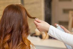 梳她他的客户的长,红色头发的美发师和洒在美容院的喷发剂 免版税库存照片