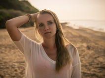 梳她的在晚上海滩的一名美丽的妇女的画象头发 库存照片
