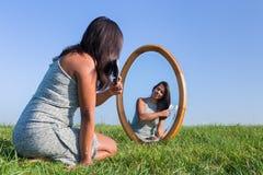 梳她的在镜子的妇女头发外面 库存图片