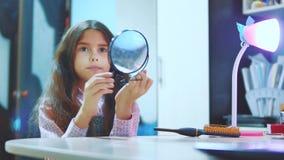 梳她的头发和看在镜子的时兴的矮小的夫人 小西班牙深色的女孩看起来敬佩 影视素材