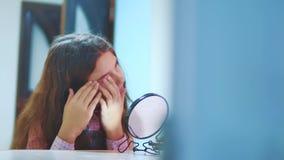 梳她的头发和看在镜子的时兴的矮小的夫人 小西班牙深色的女孩看起来敬佩 股票录像