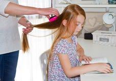 梳她的女儿的头发的母亲 免版税库存照片