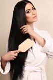 梳她的豪华健康头发的美丽的肉欲的妇女 库存图片